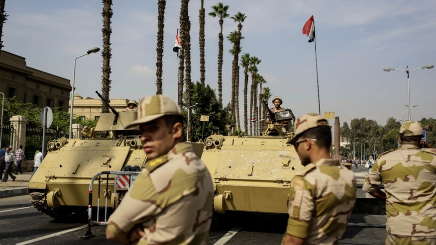 Egyptian military soldiers stand guard near a protest the day before the trial of the former President Mohammed Morsi taking place at a police academy in an eastern Cairo district, in Egypt, Sunday, Nov. 3, 2013. Morsi has been held in undisclosed destination since his ouster on July 3. He stands accused of incitement to murder. (AP Photo/Eman Helal)