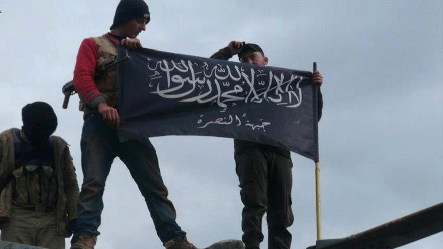 Jan. 11, 2013 - FILE photo shows rebels from al Qaeda-affiliated Jabhat al-Nusra waving brigade flag as they step on top of a Syrian air force helicopter at Taftanaz air base in northern Syria. The head of the al Qaeda-linked group fighting to topple Syrian President Bashar Assad was once a teacher of classical Arabic who joined the insurgency after he moved to Iraq, regional intelligence officials say. His whereabouts are kept so secretive that no one seems to be able to say with certainty whether he is alive or dead or where he is based.
