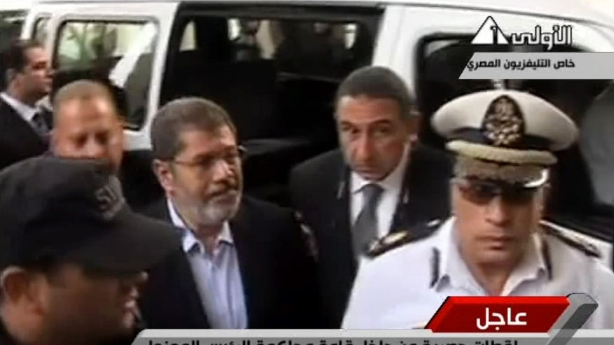 "Nov. 4, 2013 - Egyptian State Television shows ousted President Mohammed Morsi, center, arriving for a court hearing at a police academy compound in Cairo, Egypt. After 4 months in secret detention, Egypt's deposed Islamist president defiantly rejected a court's authority to try him, saying he was the country's ""legitimate"" leader and those that overthrew him should face charges instead."