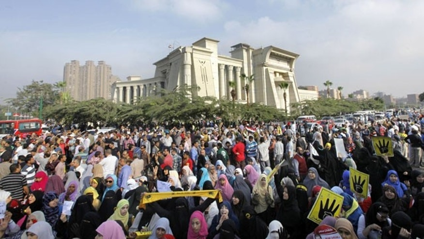 November 4, 2013: Supporters of Egypt's ousted President Mohammed Morsi protest Morsi's trial in front of the supreme constitutional court in Cairo. (AP Photo)