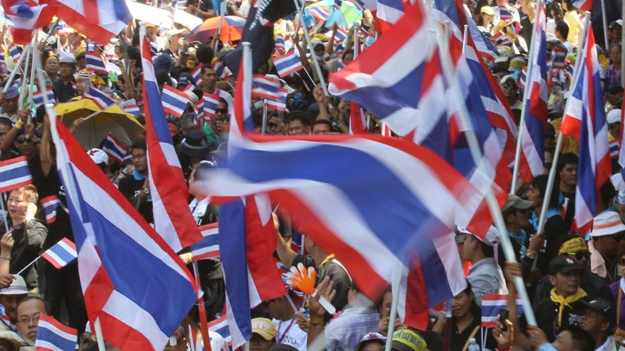 Anti-government demonstrators wave Thai national flags during a march in Bangkok, Thailand Monday, Nov. 4, 2013. Thousands of demonstrators took part in the peaceful rally against the government-proposed amnesty bill on the capital's main streets.(AP Photo/Sakchai Lalit)