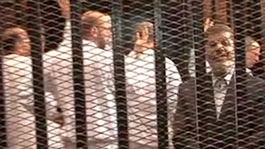 "This image made from video provided by Egypt's Interior Ministry shows ousted President Mohammed Morsi, right, speaking from the defendant's cage as he stands with co-defendants in a makeshift courtroom during a trial hearing in Cairo, Egypt, Monday, Nov. 3, 2013. Emerging from four months in secret detention, Egypt's deposed Islamist president defiantly rejected a court's authority to try him Monday, saying he was the country's ""legitimate"" leader and those that overthrew him should face charges instead.(AP Photo/Egyptian Interior Ministry)"