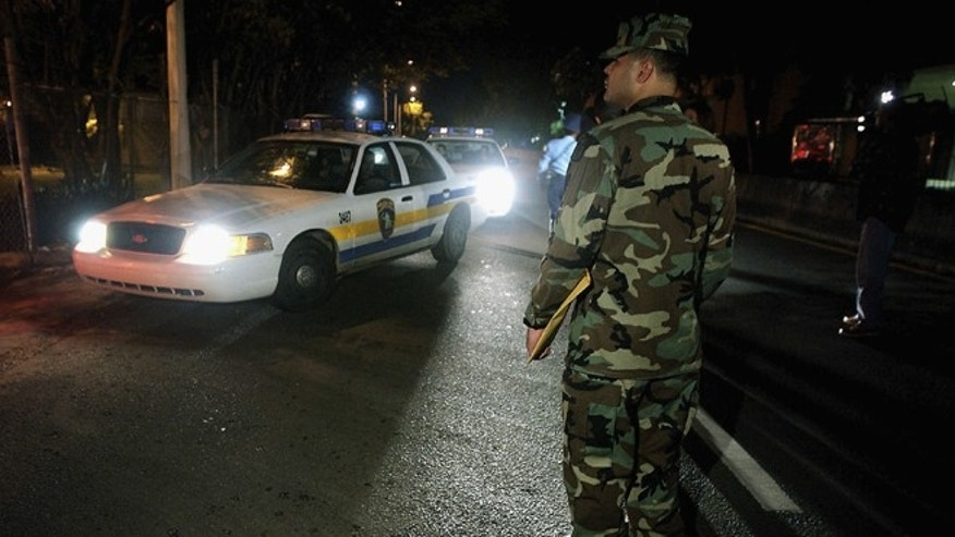 SAN JUAN, PUERTO RICO - JULY 23:  U.S. Army Captain Jose Cruzado watches several Puerto Rico Police Department vehicles go by as they start early morning patrol July 23, 2004 in San Juan, Puerto Rico. Puerto Rico Governor Sila Maria Calderon activated 500 National Guardsmen to try to bring stability after a crime wave swept the island. (Photo by Jose Jimenez/Getty Images)