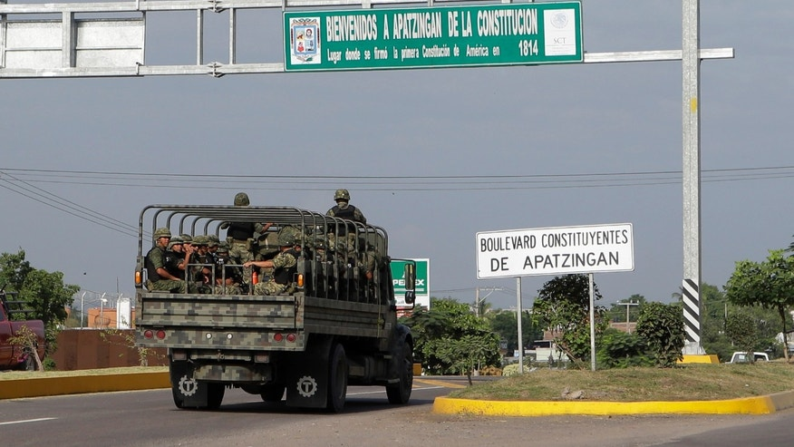 An army convoy enters Apatzingan, a town in the state of Michoacan, Mexico, Tuesday, Nov. 5, 2013. Apatzingan is located near the city of Lazaro Cardenas, where Mexico's military has taken control of one of the nation's seaports as part of an effort to bring drug-cartel activity under control in the western state of Michoacan, officials said Monday. (AP Photo/Dario Lopez-Mills)