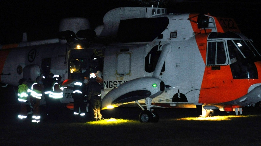 Emergency personnel surround a helicopter near the site of a bus hijacking in Aardal, western Norway, Monday, Nov. 4, 2013. A knife-wielding man on Monday hijacked a bus and killed three people on board, including the bus driver, police said. The suspect, described as a man in his 50s, was arrested after the attack in Sogn and Fjordane county, local police said. (AP Photo/NTB Scanpix, Egil Jorgen Lund) NORWAY OUT
