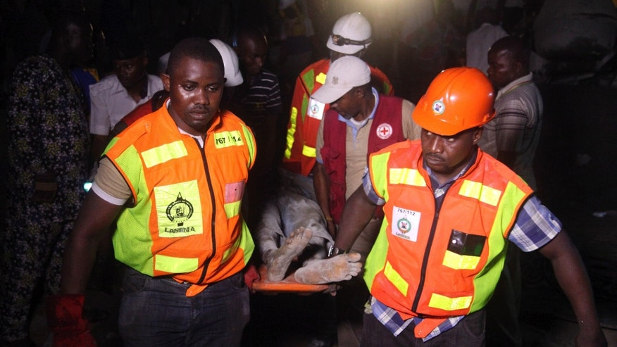 Rescue workers carry a survivor from the rubble of a building under construction which collapsed in Lagos, Nigeria, Monday, Nov, 4.  2013. Emergency officials said casualty figures from the incident were unclear as they continued their search for survivors. (AP Photo/Sunday Alamba)