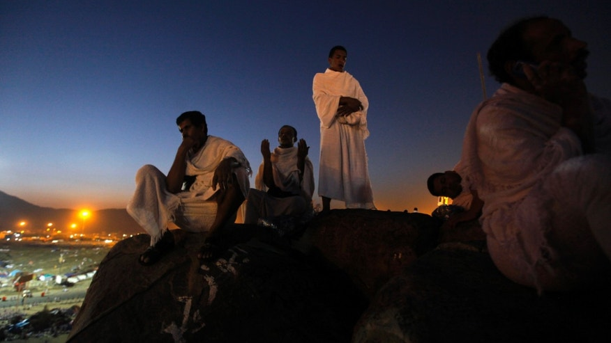 FILE - In this Monday, Oct. 14, 2013 file photo, Muslim pilgrims pray on a rocky hill called the Mountain of Mercy, on the Plain of Arafat near the holy city of Mecca. Some pilgrims who go to Saudi Arabia to perform pilgrimage stay on illegally in the kingdom in search of work. Saudi authorities are launching intensive nationwide security sweeps on businesses and setting up checkpoints in efforts to detain and deport an estimated 1.5 million foreign workers without proper documentation. The crackdown reflects wider efforts by the kingdom to clear out slums and create jobs for its local workforce as leaders worry that rising unemployment could feed dissent and challenges to their rule by their own people. (AP Photo/Amr Nabil, File)
