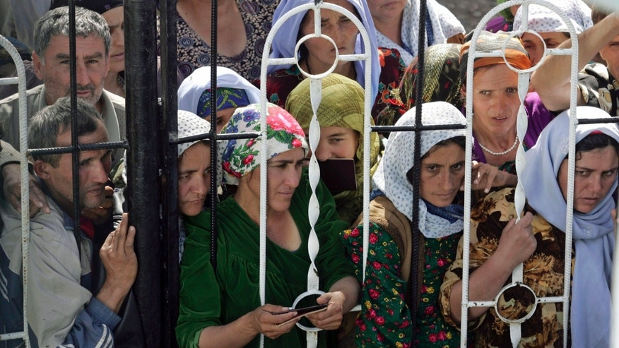 FILE - In this Friday Nov. 3, 2006 file photo, residents of Dosti, a town in southern Tajikistan, press against a fence seeking government compensation for damages caused by a strong earthquake. While the Tajik economy has gradually recovered to its Soviet-era level and has been growing over the past few years, the country remains one of the poorest nations in the former Soviet Union. Tajikistan is holding a presidential election on Wednesday, Nov. 6, 2013. (AP Photo/Sergei Grits, file)