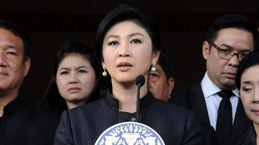In this photo released by Thai Spokesman Office, Thailand Prime Minister Yingluck Shinawatra, center, flanked by  Cabinet ministers and aides, speaks during a news conference at the government house in Bangkok, Thailand Tuesday, Nov. 5, 2013. Yingluck said the government will not interfere with the legislative process, as the Thai Senate will soon debate the controversial amnesty bill which many said was designed to bring her brother, former Prime Minister Thaksin Shinawatra, back from overseas exile.(AP Photo/Thai Spokesman Office)
