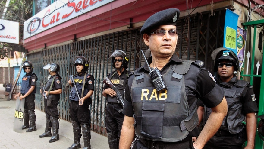 Members of Bangladesh Rapid Action Battalion (RAB) stand guard on a street outside the office of the main opposition Bangladesh Nationalist Party (BNP) during a general strike in Dhaka, Bangladesh, Monday, Nov. 4, 2013. Security was heightened across the capital, Dhaka, with extra police and paramilitary guards patrolling the streets. The opposition began a three-day strike to force the government to step down. (AP Photo/A.M. Ahad)