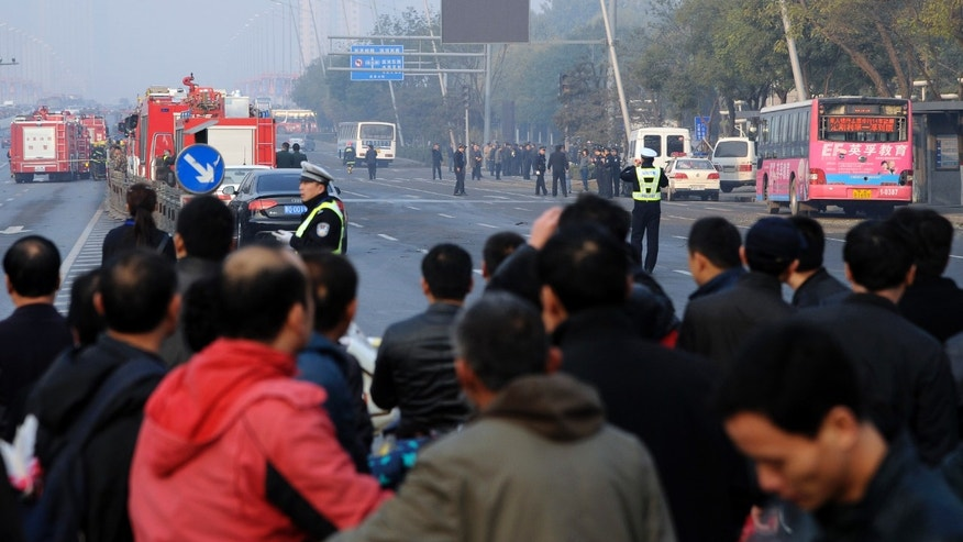 Residents gather near the site of multiple explosions outside the provincial headquarters of China's ruling Communist Party in Taiyuan in north China's Shanxi province Wednesday Nov. 6, 2013. The Shanxi provincial government and police said the blasts which killed one and injured eight struck at about 7:40 a.m. (2340 GMT Tuesday). (AP Photo) CHINA OUT