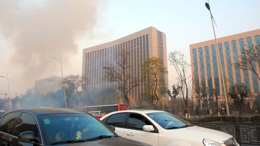 In this photo released by China's Xinhua News Agency, smoke billows from the site after explosions on the Yingze Street in Taiyuan, capital of north China' Shanxi Province, Wednesday, Nov. 6, 2013. One person was killed and several injured in a series of small explosions Wednesday outside the provincial headquarters of the ruling Communist Party in the northern Chinese city of Taiyuan, officials said. (AP Photo/Xinhua, Liu Guoliang) NO SALES