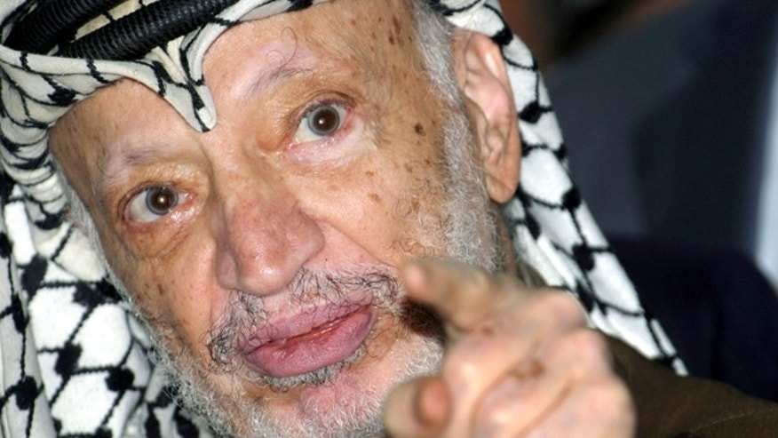 Sept. 4, 2004: Palestinian President Yasser Arafat talks to the media after opening a voter registration drive at a polling station at his headquarters in the West Bank city of Ramallah.