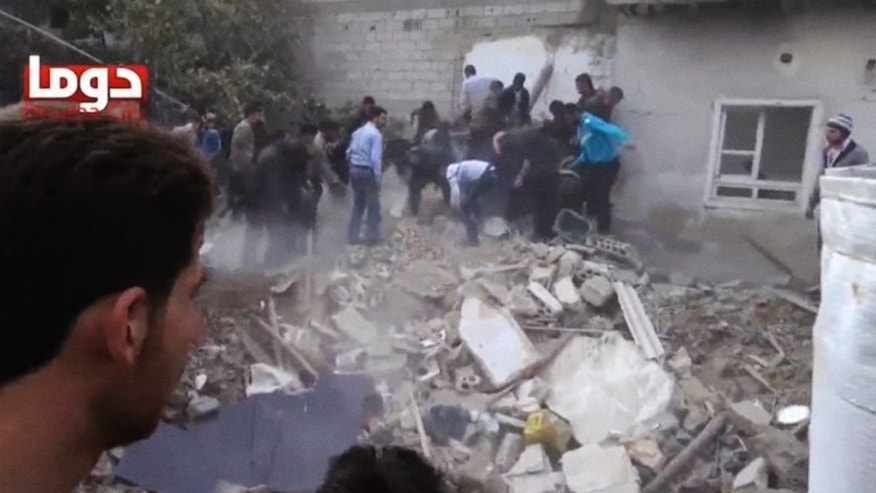 In this image taken from Monday, Nov. 4, 2013, video obtained from the Shaam News Network, which has been authenticated based on its contents and other AP reporting, people clear debris while searching for bodies in Douma, Syria. Activists said an air attack caused the ruin. (AP Photo/Shaam News Network via AP Video)