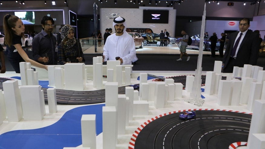An Emirati visitor plays with a remote control toy car at the Dubai International Motor Show in Dubai, United Arab Emirates, Tuesday Nov. 5, 2013. (AP Photo/Kamran Jebreili)