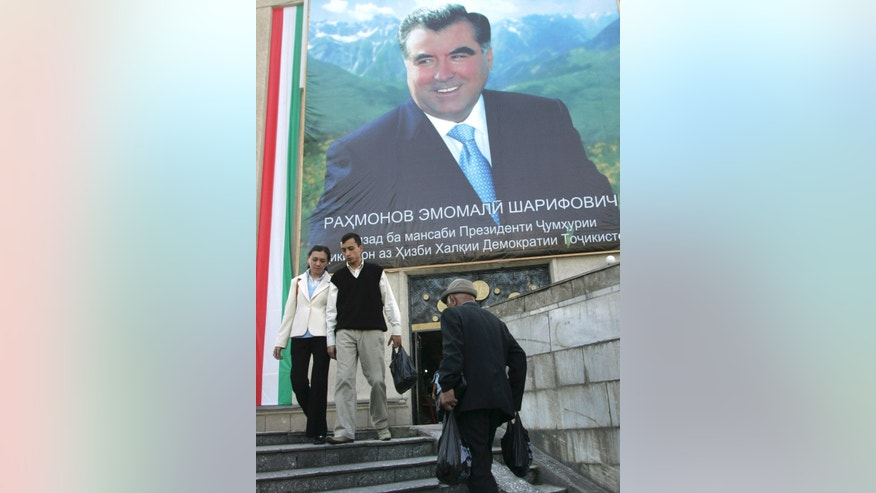 FILE - In this Wednesday, Nov. 1, 2006 file photo people walk under a giant portrait of Tajik President Emomali Rakhmon in Dushanbe, Tajikistan. Emomali Rakhmon, 61, who has led the mountainous, Sunni Muslim nation neighboring Afghanistan and China for more than two decades, is all but certain to win a fourth presidential term in the vote on Wednesday Nov. 6th, 2013. (AP Photo/Sergei Grits, File)