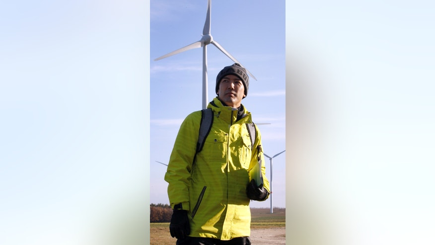 FILE - In this Nov. 30, 2011 file photo, Japan's anti-nuclear activist actor Taro Yamamoto looks at windmills during a visit to a wind farm of the village of Feldheim near Berlin, when residents of the radiation-stricken area around Japan's tsunami-hit nuclear reactors of Fukushima visit Germany to learn how renewable energy could work in their homeland. The actor-turned-novice lawmaker has caused an uproar in Japan by doing something taboo: handing a letter to the emperor - a gesture considered both impolite and inappropriate. The ruckus began at an Imperial Palace garden party last week. Yamamoto, 38, said he only wanted to make an appeal to the emperor about the crisis in Fukushima and its possible health impact on residents and workers cleaning up the power plant, which was devastated by the 2011 earthquake and tsunami. (AP Photo/Michael Sohn, File)
