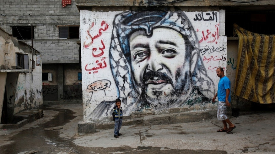 "Palestinians walk past a mural depicting late Palestinian leader Yasser Arafat at Shati Refugee Camp, in Gaza City, Thursday, Nov. 7, 2013. Swiss scientists have found evidence suggesting Yasser Arafat may have been poisoned with a radioactive substance, a TV station reported on Wednesday, prompting new allegations by his widow that the Palestinian leader was the victim of a ""shocking"" crime. Arabic reads, ""the leader Abu Ammar, you are in our hearts, your sun will not go down."" (AP Photo/Adel Hana)"