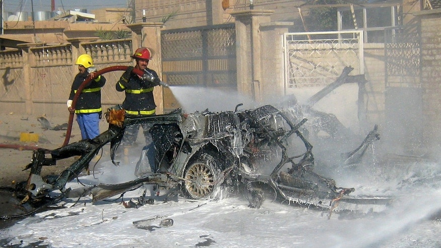 Iraqi firefighters hose down a burned car after a car bomb attack in Kirkuk, 180 miles (290 kilometers) north of Baghdad, Iraq, Tuesday, Nov. 5, 2013. A parked car bomb went off in front of Iraqi Islamic Bank in Kirkuk, home to a mix of Arabs, Kurds and Turkomen, each of the ethnic groups has competing claims to the oil-rich area, the Kurds want to incorporate it into their self-ruled region in Iraq's north, but Arabs and Turkomen are opposed. (AP Photo/Emad Matti)