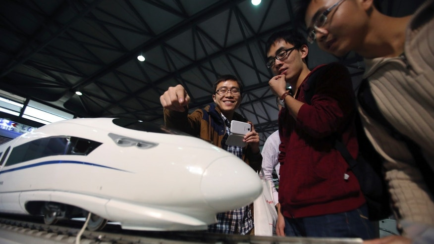 In this Nov. 5, 2013 photo, visitors look at a scale model of the latest Chinese high-speed train at China International Industry Fair in Shanghai, China. Facing pressure to overhaul a worn-out growth model, China's leaders are promising dramatic changes at a weekend meeting, starting on Saturday, Nov. 9, 2013, that reform advocates hope will make history by unleashing a new wave of economic transformation. (AP Photo/Eugene Hoshiko)