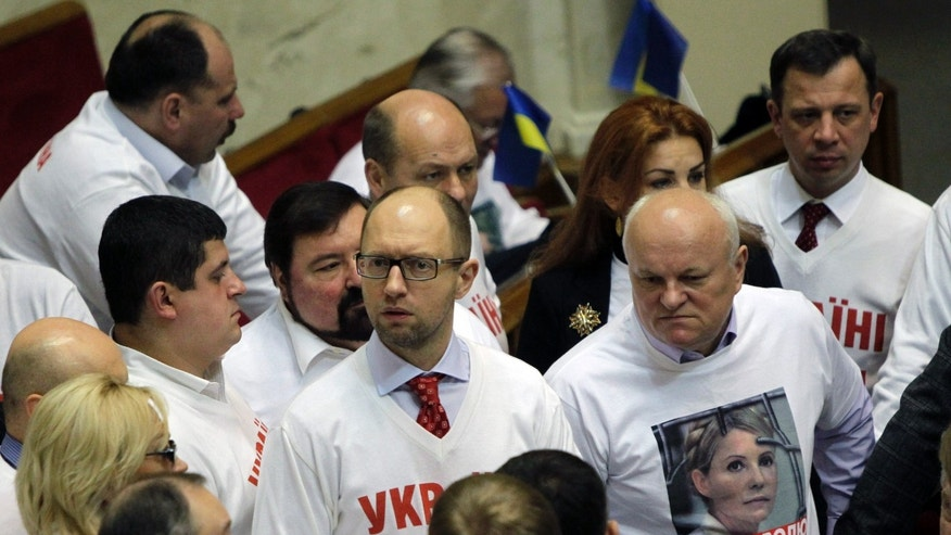 Ukrainian opposition leader Arseniy Yatsenyuk, centre talks to lawmakers in the parliament session hall, in Kiev, Ukraine, Thursday, Nov. 7, 2013. A vote on various bills that would allow former Ukrainian Prime Minister Yulia Tymoshenko to go to Germany from prison is scheduled for Thursday. The words emblazoned on his shirt reads,'Freedom for Yulia.' (AP Photo/Sergei Chuzavkov)