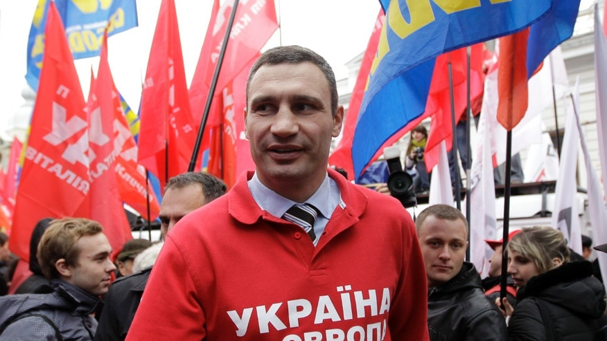 Lawmaker and chairman of the Ukrainian opposition party Udar (Punch), WBC Heavyweight Champion boxer Vitali Klitschko, center, attends a rally in front of parliament building in Kiev, Ukraine, Thursday, Nov. 7, 2013. A vote on various bills that would allow former Ukrainian Prime Minister Yulia Tymoshenko to go to Germany from prison is scheduled for Thursday.  The words emblazoned on this shirt reads, 'Ukraine is Europe'.  (AP Photo/Sergei Chuzavkov)