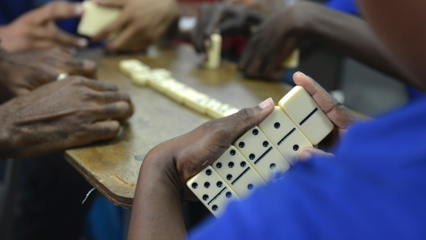 "In this Oct. 31, 2013 photo, vocational students learn domino strategies in a classroom in Kingston, Jamaica. A government program is teaching domino strategies to inner-city young adults from gang-steeped areas. Under the guidance of a Justice Ministry officer who devised the ""Dominoes for Life"" program, participants say the game is helping them work through possible outcomes and develop thinking skills as they learn how to better connect the dots in the real world. (AP Photo/David McFadden)"