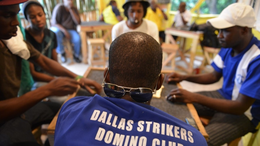 In this Nov. 3, 2013 photo, a member of the Dallas Strikers Domino Club wears his team's shirt for a competitive match in Constitution Hill, a rural mountain on the outskirts of Kingston, Jamaica.  The centuries-old matching game is deeply woven into the cultural fabric of the Caribbean, from the beaches of Barbados to the plazas of Puerto Rico. (AP Photo/David McFadden)