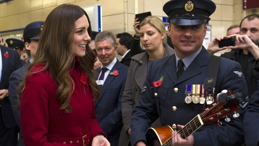 Nov. 7, 2013: Kate, the Duchess of Cambridge, left, reacts with an unidentified member of the Royal British Legion,  at Kensington High Street Station, in London.