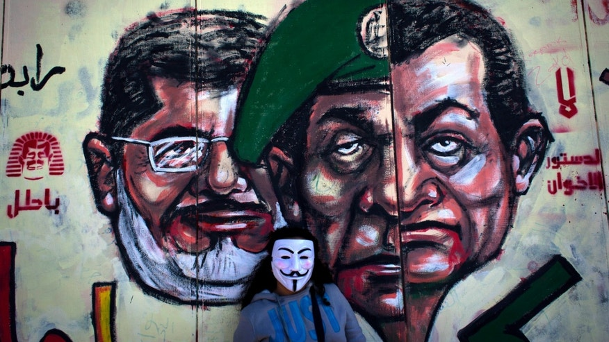 "FILE - In this Dec. 8, 2012 file photo, an Egyptian protester wears a Guy Fawkes mask while posing for a photo next to a mural painted overnight on the exterior  wall of the presidential palace depicting president Mohammed Morsi, left, former military council ruler Hussein Tantawi, center and ousted President Mubarak with Arabic that reads ""No, the brotherhood's constitution is not valid, in Cairo. Egyptian authorities switched the venue for the trial of the former Islamist president on Sunday, Nov. 3, 2013 a last-minute change made after the Muslim Brotherhood called for mass demonstrations at the original location. The trial of Morsi, now to be held east of the capital on Monday, could lead to another round of bloodshed as his supporters look likely to face an emboldened security apparatus that has boosted its forces for the hearing.(AP Photo/Nasser Nasser, File)"