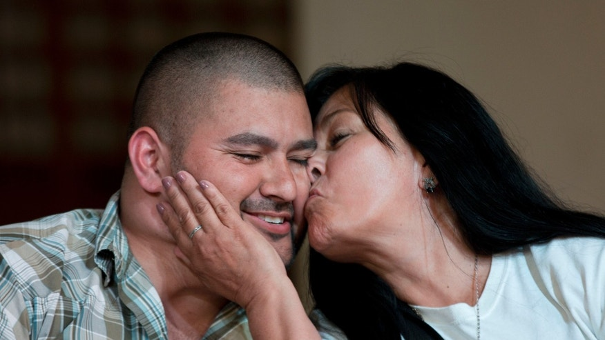 Guadalupe Melendez kisses her son Israel Arzate during a news conference in Mexico City, Thursday, Nov. 7, 2013. Human rights groups are welcoming a Mexican Supreme Court decision to free Azarte who claimed soldiers tortured him into confessing to a role in a drug-related massacre. The court ruled the 28-year-old's confession wasn't valid because he talked to soldiers rather than prosecutors, as the law requires. (AP Photo/Eduardo Verdugo)