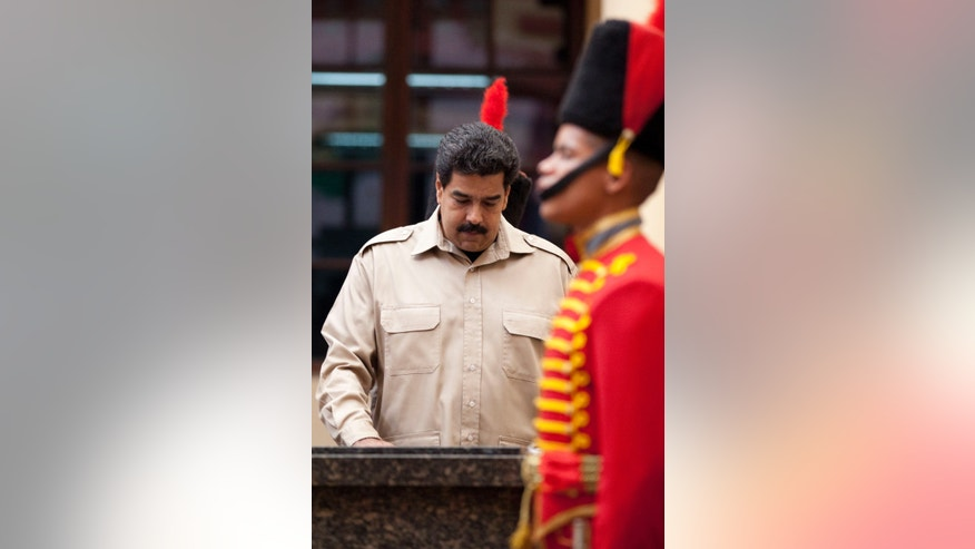 Venezuela's President Nicolas Maduro visit the tomb of the late President Hugo Chavez, at the Military Museum in Caracas, Venezuela, Tuesday, Nov. 5, 2013. Maduro's decree establishing Dec. 8 as a public holiday in honor of Chavez was announced Tuesday. The holiday will commemorate Chavez's final public appearance, when the cancer stricken leader anointed Maduro as his successor. (AP Photo/Ariana Cubillos)