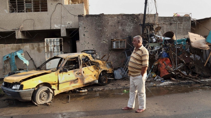 An Iraqi man inspects his car destroyed in a suicide car bomb in the Baghdad al-Jadidah district, Iraq, Friday, Nov. 8, 2013. Officials in Iraq said a series of attacks, including a bomb attack have killed and wounded civilians on Thursday. (AP Photo/Khalid Mohammed)
