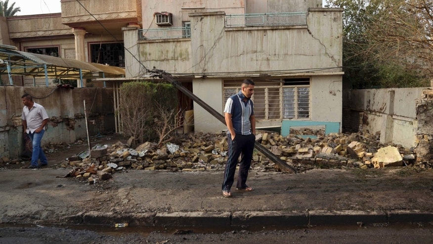 Civilians inspect their damaged house at the site of a suicide car bomb in the Baghdad al-Jadidah district, Iraq, Friday, Nov. 8, 2013. Officials in Iraq said a series of attacks, including a bomb attack have killed and wounded civilians on Thursday. (AP Photo/ Khalid Mohammed)