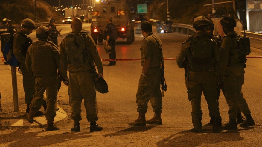 "Israeli soldiers stand at the scene of a shooting at a checkpoint in the West Bank near Nablus, Thursday, Nov. 7, 2013. The Israeli military says soldiers shot a Palestinian man to death after he fired an ""improvised weapon"" at a bus stop in the West Bank. Israeli police said he was launching fireworks. (AP Photo / Nasser Ishtayeh)"