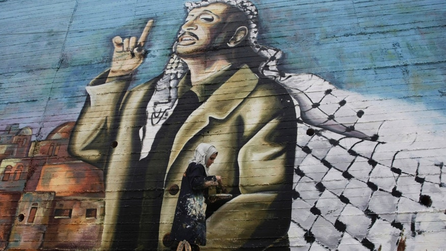 "Palestinian Hanadi Kharma, paints a mural depicting the late Palestinian leader Yasser Arafat in the West Bank city of Nablus, Thursday, Nov. 7, 2013. Swiss scientists have found evidence suggesting Yasser Arafat may have been poisoned with a radioactive substance, a TV station reported on Wednesday, prompting new allegations by his widow that the Palestinian leader was the victim of a ""shocking"" crime. (AP Photo/Nasser Ishtayeh)"