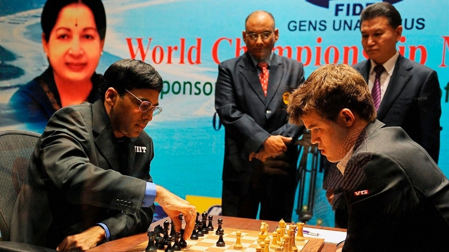 Defending champion Indias Viswanathan Anand, left, makes a move against Norways Magnus Carlsen during the first game of the World Chess Championship in Chennai, India, Saturday, Nov. 9, 2013. The game ended in a draw. (AP Photo)