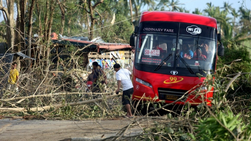 People remove fallen trees from a road in Daanbantayan town, north Cebu, central Philippines, after typhoon Haiyan hit the region, Sunday, Nov. 10, 2013. Typhoon Haiyan, one of the most powerful storms on record, slammed into six central Philippine islands on Friday, leaving a wide swath of destruction and scores of people dead. (AP Photo/Chester Baldicantos)