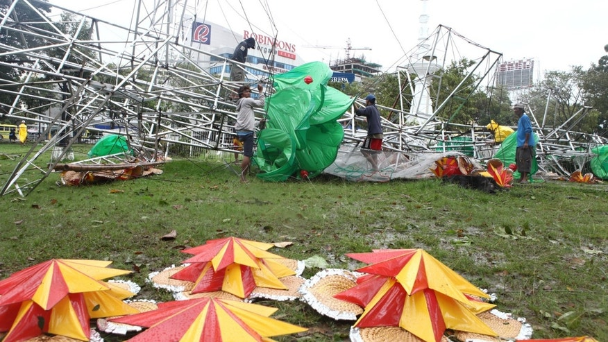 In this Nov. 8, 2013 photo, a gigantic Christmas tree is toppled by strong wind caused by typhoon Haiyan, at Fuente Osmena Circle, Cebu, Philippines. Typhoon Haiyan, one of the most powerful storms on record, slammed into six central Philippine islands on Friday, leaving a wide swath of destruction and scores of people dead.  (AP Photo/Chester Baldicantos)