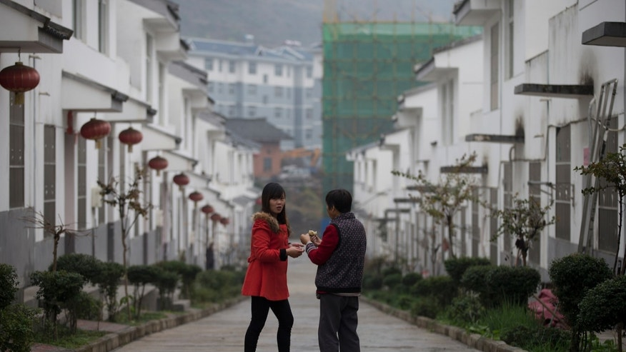 In this Tuesday, Nov. 5, 2013 photo, Chinese women chat near a housing block built for rural citizens, in Qiyan in China's Shaanxi province. Originally started as a disaster resettlement in 2010, Qiyan Community has since been swept into China's massive push to move millions of country folk into more urban settings to improve access to services and to shift away from a factory-based economy. But for most families, there is no work in Qiyan, meaning that most of the region's working-age people must still travel elsewhere for jobs. (AP Photo/Andy Wong)