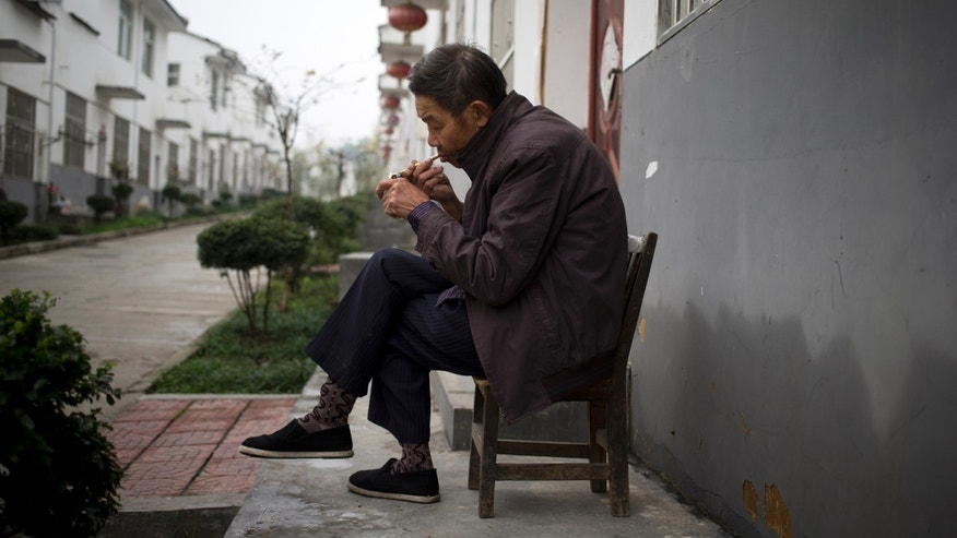 In this Tuesday, Nov. 5, 2013 photo, a man lights his cigarette outside his new house in Qiyan, in China's Shaanxi province. Originally started as a disaster resettlement in 2010, Qiyan Community has since been swept into China's massive push to move millions of country folk into more urban settings to improve access to services and to shift away from a factory-based economy. But for most families, there is no work in Qiyan, meaning that most of the region's working-age people must still travel elsewhere for jobs. (AP Photo/Andy Wong)