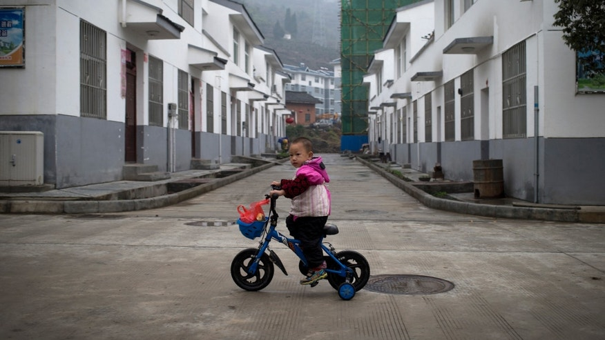 In this Tuesday, Nov. 5, 2013 photo, a child rides a bicycle past a housing block for rural citizens, in Qiyan, in China's Shaanxi province. Originally started as a disaster resettlement in 2010, Qiyan Community has since been swept into China's massive push to move millions of country folk into more urban settings to improve access to services and to shift away from a factory-based economy. But for most families, there is no work in Qiyan, meaning that most of the region's working-age people must still travel elsewhere for jobs. (AP Photo/Andy Wong)