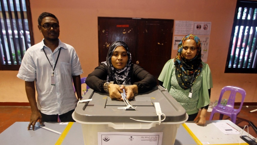 An election official breaks the seal of a ballot box to count votes after polling for presidential elections closed in Male, Maldives, Saturday, Nov. 9, 2013.  After two months of political bickering and repeated failure to hold a presidential election, people in the Maldives voted Saturday to elect a new leader for their budding but vulnerable democracy. (AP Photo/Sinan Hussain)