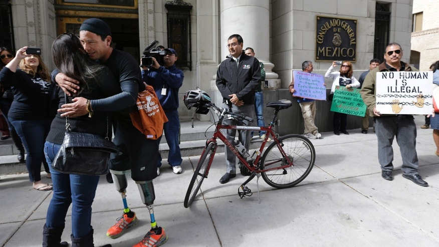 Cyclist Carlos Gutierrez, a double amputee, center, gets a hug from a supporter during a stop at the Mexican Consulate, Thursday, Nov. 7, 2013, in San Antonio. Gutierrez, a Mexican asylum seeker who fled to the U.S. after extortionists cut his legs off for not paying the extortion fees, is riding his bike from El Paso, Texas to Austin, Texas, to raise awareness on the situation of political asylum seekers.  (AP Photo/Eric Gay)