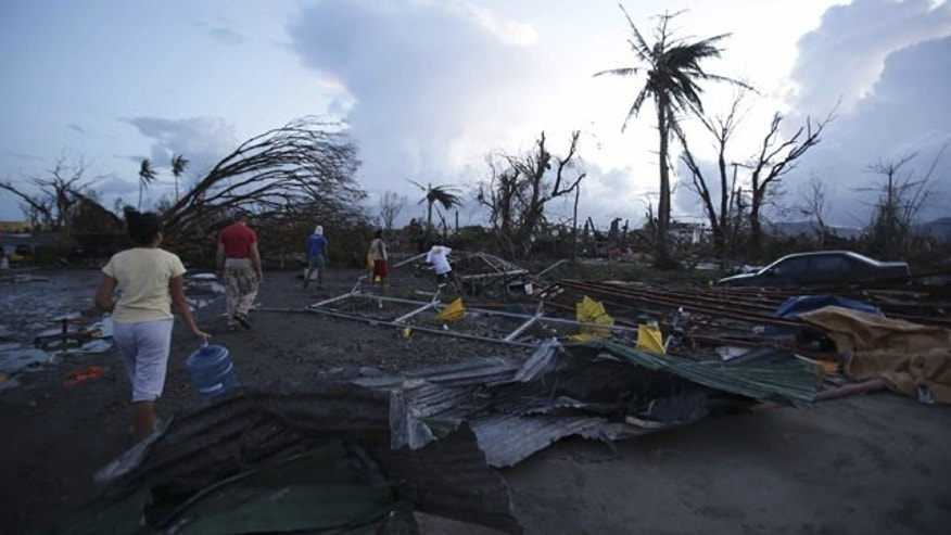 November 9, 2013: Residents walk by debris after powerful Typhoon Haiyan slammed into Tacloban city, Leyte province, central Philippines. (AP Photo)