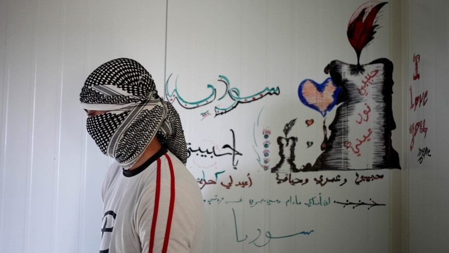 "In this Tuesday, Nov. 5, 2013 photo, Abu Abdullah Hourani, 27, stands near a drawing on the wall of his shelter with Arabic that reads, ""my love, my life, Syria,"", during his interview with The Associated Press, at the Zaatari refugee camp near the Syrian border. n the bustling marketplace of this sprawling camp for Syrian refugees, a mosque preacher appeals to worshippers to join their countrymen in the fight to topple President Bashar Assad. In another corner of the Zaatari camp, two men draped in the Syrian rebel flag call on refugees through loudspeakers to sign up for military training. Rebels in the camp freely acknowledge recruiting fighters in the camp in a drive that has increased since the summer. (AP Photo/Mohammad Hannon)"