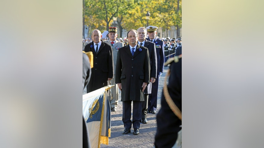 French President Francois Hollande, prime minister Jean-Marc Ayrault, second right, and defence minister Jean-Yves Le Drian, left, take part in a ceremony at the Arc de Triomphe in Paris, Monday Nov. 11, 2013. President Francois Hollande reviewed troops around Paris' iconic Arc de Triomphe and laid a wreath on the tomb of the unknown soldier beneath the arch to commemorate France's war dead. Nov. 11 marks the signing of the truce that ended the fighting in World War I. (AP Photo/Remy de la Mauviniere/Pool)