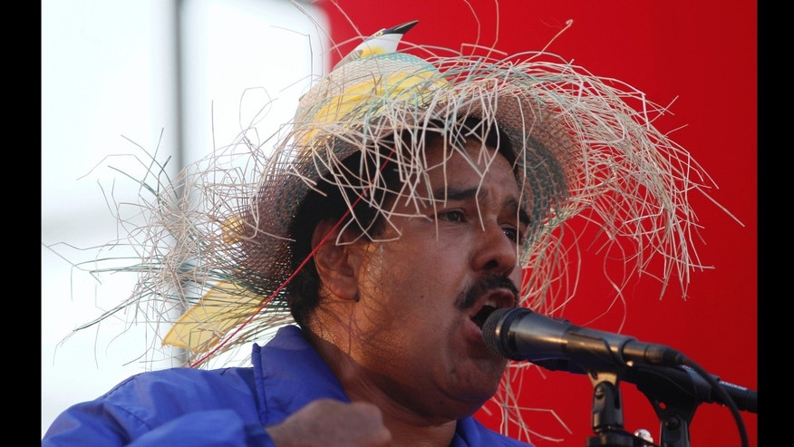 Venezuela's acting President Nicolas Maduro wears a farm worker's hat with the figure of a bird perched on the hat's crown as he speaks during a presidential election campaign rally.
