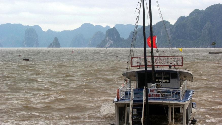 A tourist boat is seen sinking in Ha Long Bay, Vietnam Monday, Nov. 11, 2013. Typhoon Haiyan made landfall in northern Vietnam early Monday as a tropical storm, just days after leaving massive destruction in the Philippines. (AP Photo/Hau Dinh)