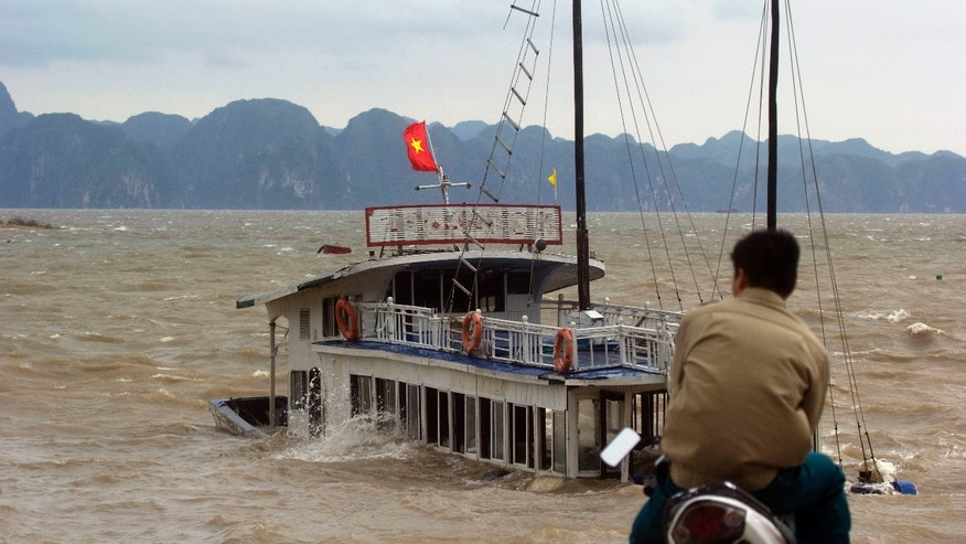 A man looks at a tourist boat sinking in Ha Long Bay, Vietnam Monday, Nov. 11, 2013. Typhoon Haiyan made landfall in northern Vietnam early Monday as a tropical storm, just days after leaving massive destruction in the Philippines. (AP Photo/Hau Dinh)